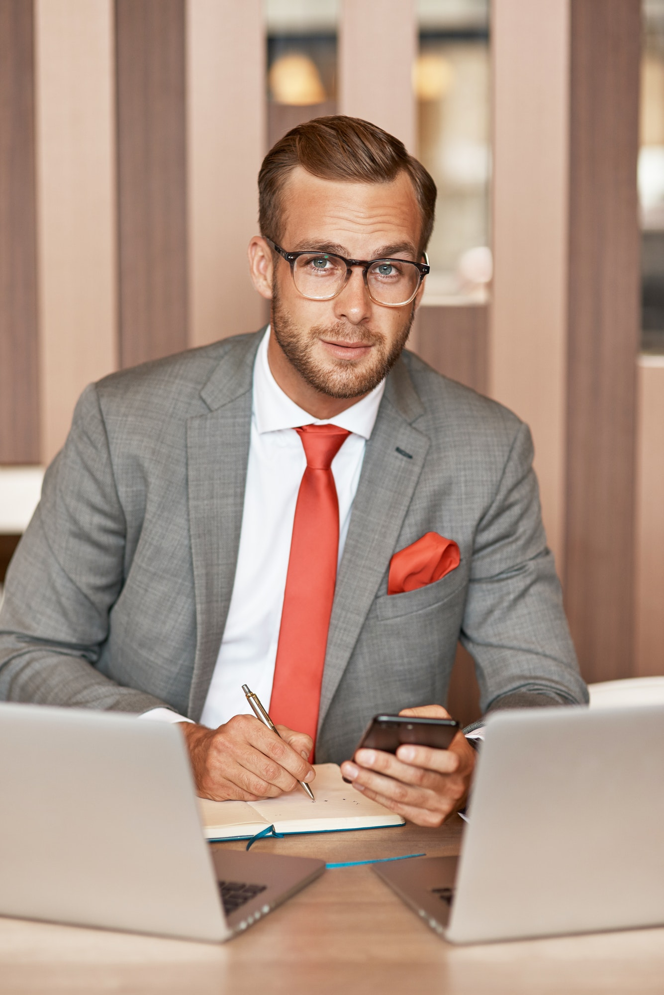 Positive young businessman sitting in the office