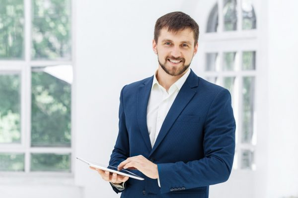 Elegant successful  businessman standing at the office and looking throw the information on his laptop